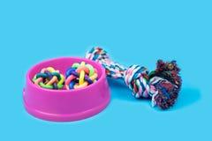 Bacia do animal de estimação, corda e bola de borracha em claro - fundo azul imagem de stock royalty free