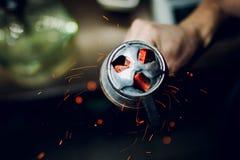 Bacia do cachimbo de água com carvões encarnados nas mãos de um cachimbo de água em um fumo escuro do fundo fotos de stock