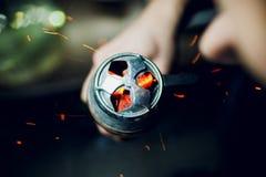 Bacia do cachimbo de água com carvões encarnados nas mãos de um cachimbo de água em um fumo escuro do fundo fotografia de stock royalty free