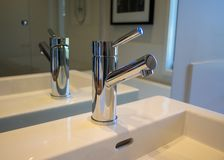Bacia do dissipador do torneira e da porcelana do cromo do banheiro foto de stock royalty free