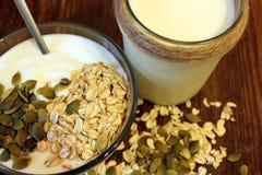 Bacia do iogurte grego com farinha de aveia e sementes na tabela de madeira Fotografia de Stock Royalty Free