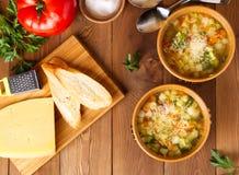 Bacia dois de sopa do minestrone com queijo na placa e nos vegetais de corte no fundo de madeira rústico, vista superior Imagens de Stock