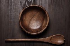 Bacia e colher de madeira de salada na tabela Fotografia de Stock