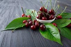 Bacia fresca das cerejas na madeira branca Fotografia de Stock