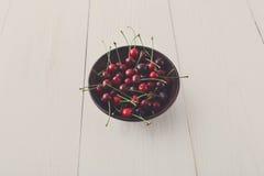 Bacia fresca das cerejas na madeira branca Imagens de Stock