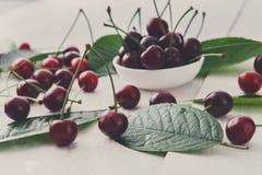 Bacia fresca das cerejas na madeira branca Fotos de Stock Royalty Free