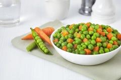 Bacia fresca de feijões verdes e de cenouras cubadas no fundo branco Foto de Stock