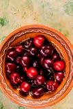 Bacia grande com muitas grandes cerejas doces saborosos suculentas vermelhas Bagas frescas das cerejas na bacia no fundo de madei foto de stock