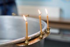 Bacia grande de água para o batismo de um bebê com velas da cera orthodoxy Católicos gregos Macro fotografia de stock