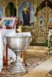 Bacia ortodoxo de água santamente e de velas para batizar Imagens de Stock