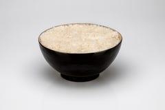 Bacia preta com arroz, no fundo branco Imagem de Stock