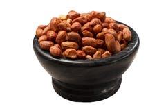 A bacia preta com os amendoins no branco isolou o fundo Fotos de Stock Royalty Free