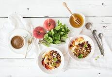 Bacia saudável do café da manhã de granola da aveia com iogurte, fruto fresco, hortelã e mel Fotos de Stock