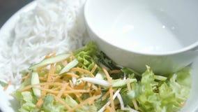 Bacia vazia na placa perto dos macarronetes e da salada da vitamina do fim da cenoura, do pepino e da alface acima O cozinheiro p vídeos de arquivo