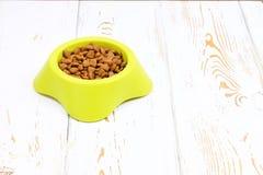 Bacia verde-amarela com comida de gato seca em um assoalho de madeira branco Imagem de Stock Royalty Free