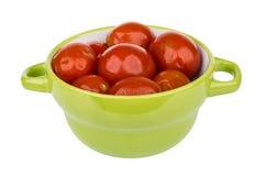 A bacia verde com vermelho pôs de conserva os tomates isolados no branco Fotografia de Stock