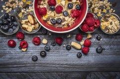 Bacia vermelha com as bagas do muesli, as nuts e as frescas no fundo rústico azul, vista superior, beira Imagens de Stock