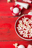 Bacia vermelha com as flores brancas na água, garrafa com loção na tabela de madeira, fundo dos termas Fotografia de Stock