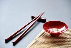 Bacia vermelha e hashis de madeira vermelhos fotografia de stock royalty free