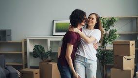 Baciare ballante di amore della moglie e del marito divertendosi a casa durante la rilocazione video d archivio