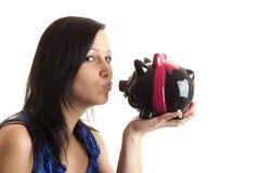 Baciare della banca piggy della giovane donna immagine stock