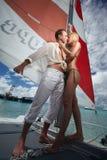 Baciare delle coppie di Gorgerous, stante sulla barca a vela, catamarano sotto Immagini Stock