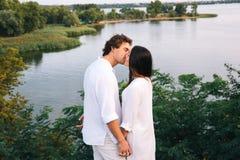 Baciare le coppie sui precedenti del fiume vicino al fogliame Fotografia Stock