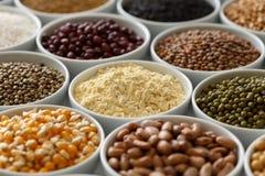 Bacias brancas arranjadas com pulsos crus, grões e sementes em w fotografia de stock royalty free