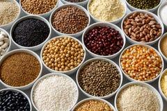Bacias brancas arranjadas com pulsos crus, grões e sementes em w fotografia de stock