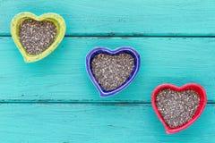 Bacias cerâmicas da forma do coração com sementes de Chia Fotografia de Stock Royalty Free