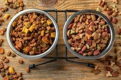 Bacias com alimentos para animais de estimação no fundo de madeira imagem de stock