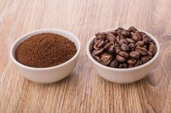 Bacias com café à terra e os feijões de café roasted na tabela Fotos de Stock Royalty Free