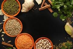 Bacias com leguminosa e especiarias do indiano, fresco e secado em b preto Fotos de Stock