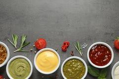 Bacias com molhos e os ingredientes diferentes, configuração lisa Espa?o para o texto foto de stock