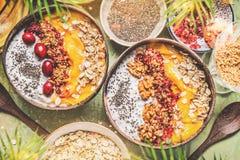 Bacias da manga do batido com pudim do iogurte das sementes do chia e arandos, porcas, farinha de aveia que cobre em escudos com  fotografia de stock