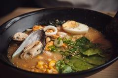 Bacias de sopa asiática com marisco, ovos, cebola fotografia de stock
