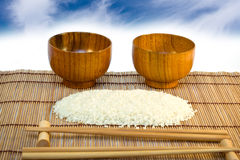 Bacias e arroz na esteira de madeira com varas Foto de Stock Royalty Free
