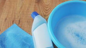 Bacino con acqua del sapone, il detersivo e lo straccio di pulizia stock footage