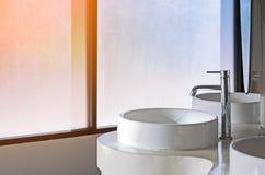 Bacino e rubinetto bianchi del lavandino del lavaggio nell'interno della toilette con w Fotografia Stock Libera da Diritti
