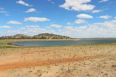Bacino idrico con i livelli dell'acqua retrocedere ed il cielo blu luminoso immagini stock