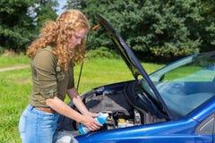 Bacino idrico di riempimento dell'automobile della ragazza olandese con liquido in bottiglia fotografia stock libera da diritti