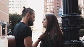 Bacio caucasico millenario delle coppie in via della città Tipo e ragazza romantici dei pantaloni a vita bassa nella relazione ro stock footage