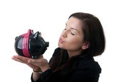 Bacio del piggybank della giovane donna Fotografia Stock
