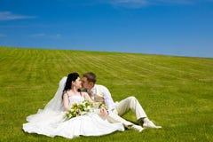 Bacio delle coppie nuovo-sposate sull'erba Immagini Stock