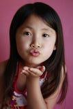 Bacio di salto della piccola ragazza asiatica Fotografia Stock