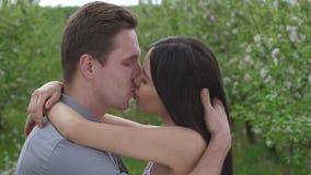 Bacio romantico di giovani coppie nell'amore in frutteto video d archivio