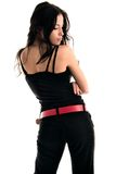 Back. Young woman in black trousers and shirt with red belt Stock Image