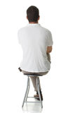 Back. An adult man sitting on a stool, with his back facing the camera Stock Photo