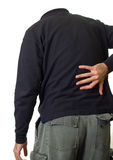 Back Ache. A person holding their lower back in pain Stock Photo