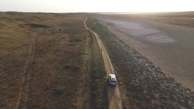Back aerial view: Big silver SUV driving in a steppe in front of the sunset stock video footage